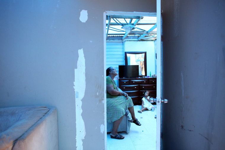 Image: Milagros Nolazco sits in her bedroom and near her granddaughter Isya, as a plastic sheet replaces the roof hit by Hurricane Maria in September, in a neighbourhood in Canovanas