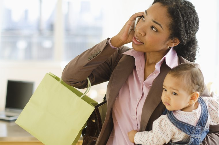 Image: Mixed race woman holding baby and talking on cell phone