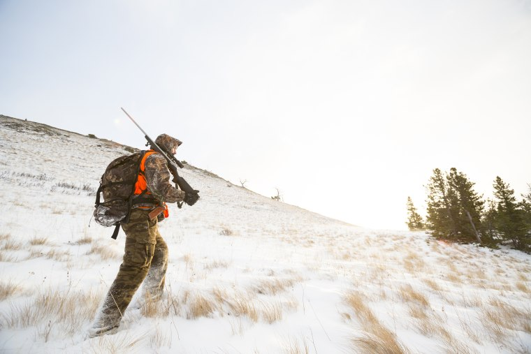 Image: A male hunter at sunrise in the snow.