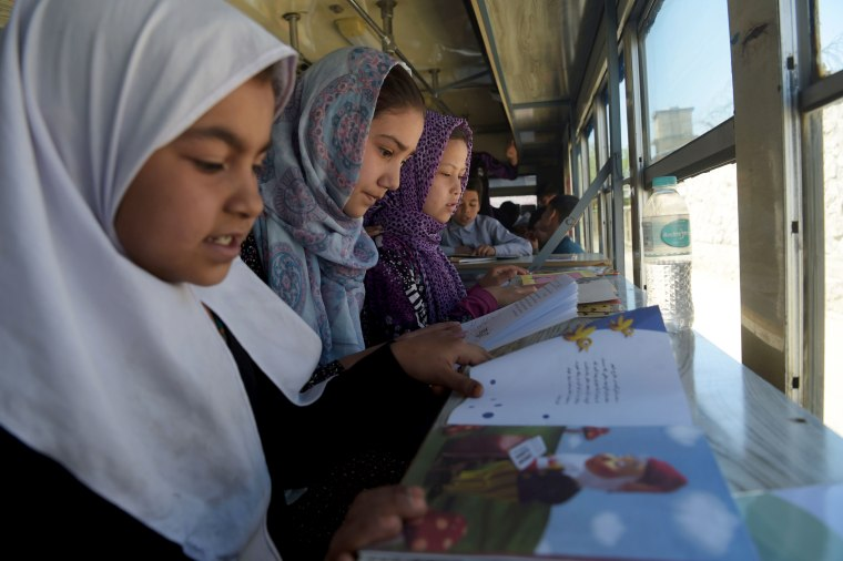 Image: Afghan children read books in a mobile library bus in Kabul, April 4, 2018.