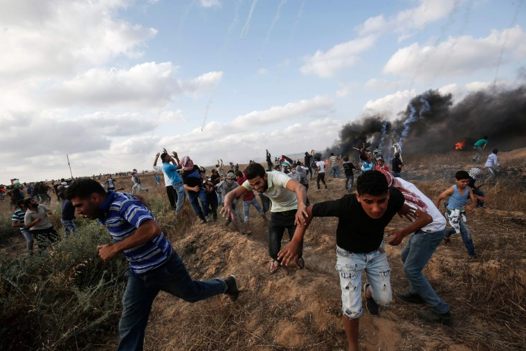 Image: Palestinian protesters flee from incoming tear gas canisters during clashes following a demonstration along the border with Israel east of Khan Yunis in the southern Gaza strip on June 1, 2018.