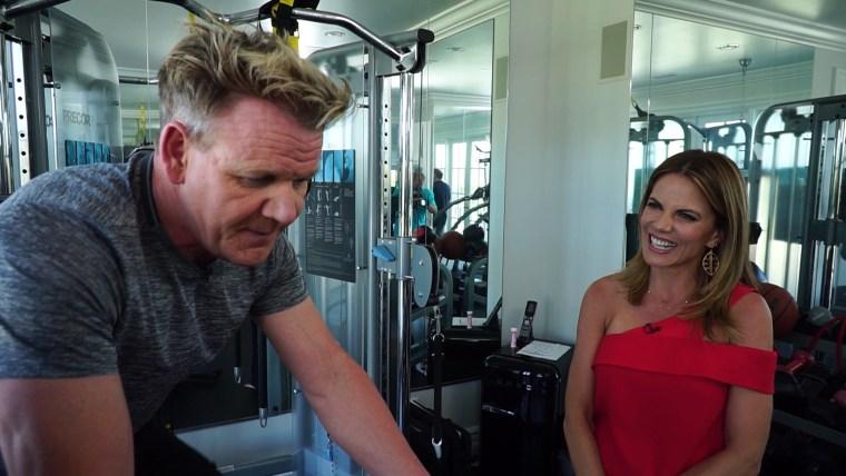 Gordon Ramsey exercises on a bike next to Natalie Morales