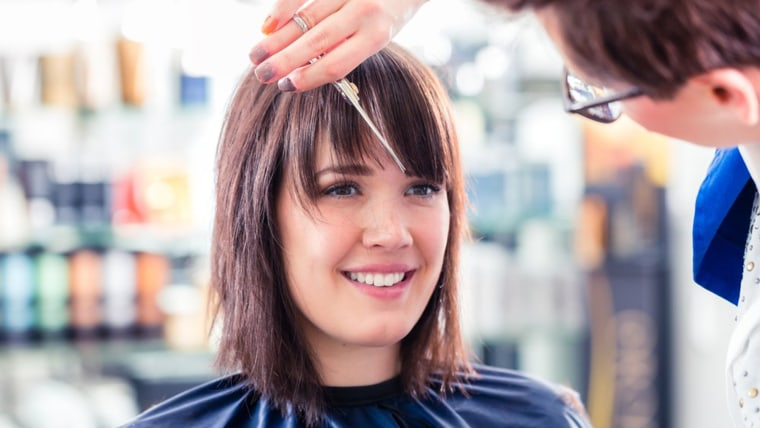 Woman cutting bangs at the salon