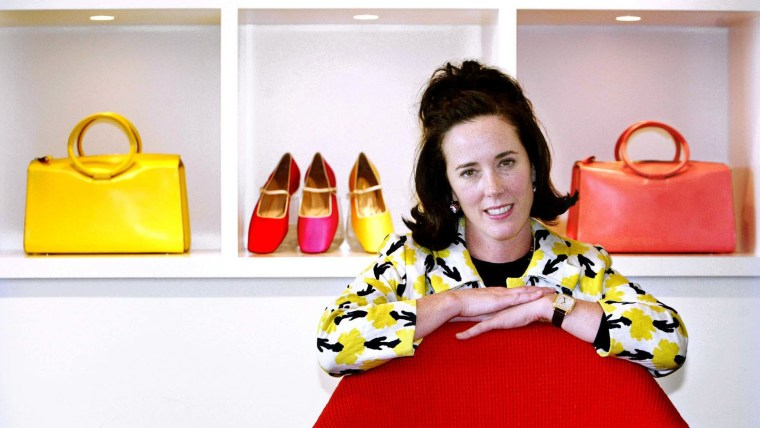 Kate Spade poses with handbags