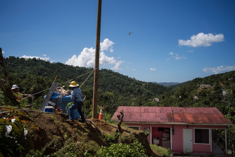 Image: Workers secure a pole that was lowered into place by a helicopter in the mountainous area of San Germ?n in western Puerto Rico.