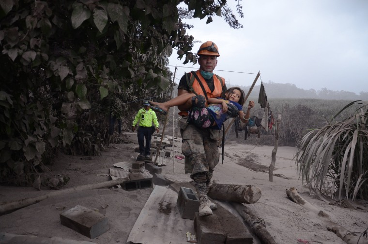 Image: A Guatemalan rescue team member carries a girl in El Rodeo, Guatemala