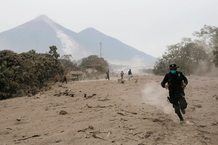 Image: A police officer runs away from a new pyroclastic flow spewed by the Fuego volcano in the community of San Miguel Los Lotes in Escuintla