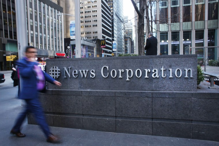 Image: A man walks by the News Corporation headquarters