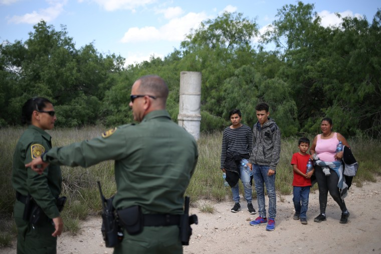 Image: People who illegally crossed the Mexico-U.S. border turn themselves in to U.S. Border Patrol agents near McAllen