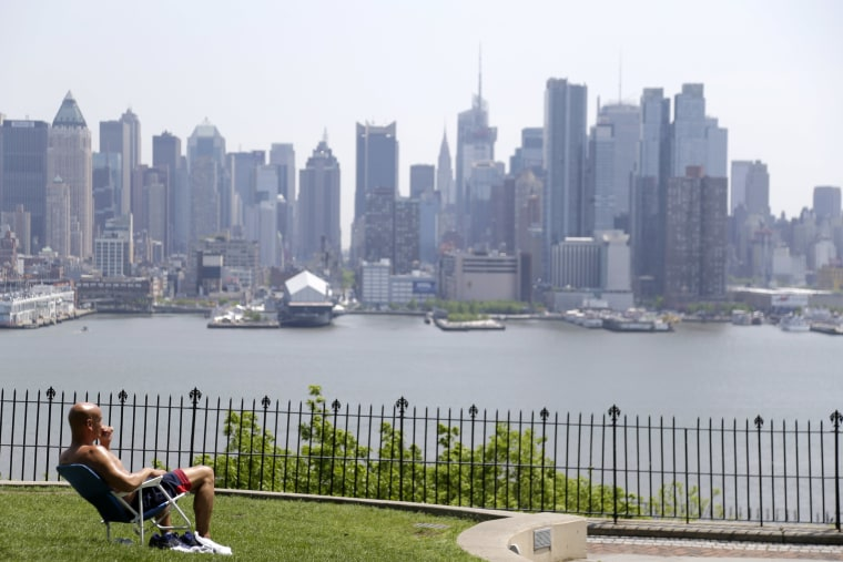 Image: A man enjoys the sunshine and the New York City skyline from a park