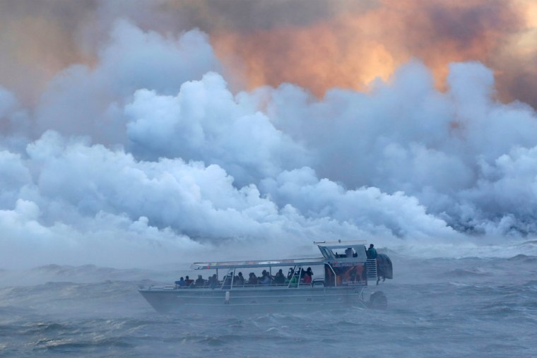 Image: People watch from a tour boat as lava flows into the Pacific Ocean in the Kapoho area, east of Pahoa