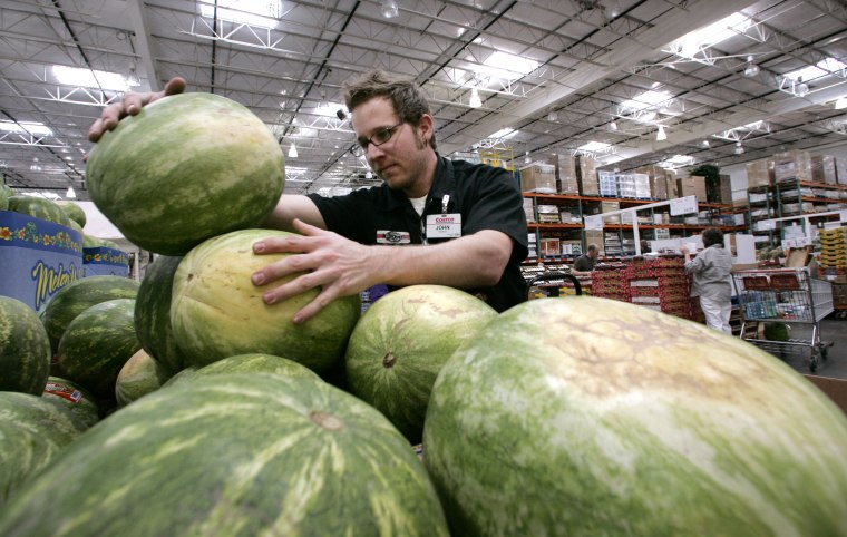 Image: A Costco produce stocker stacks watermelons on May 29, 2008.