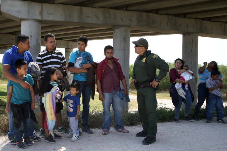Image: A border patrol agent with immigrants who illegally crossed the border from Mexico into the U.S. in the Rio Grande Valley sector, near McAllen