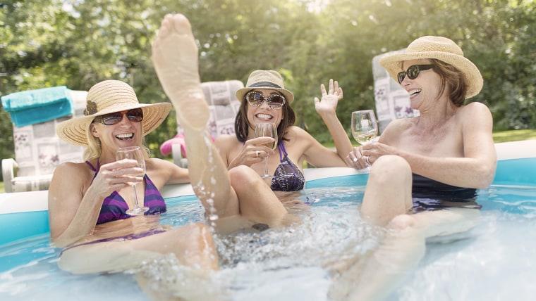 Three mature women sitting in paddling pool, drinking wine