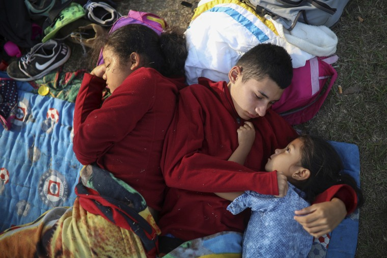 Image: Siblings from El Salvador huddle together on a soccer field