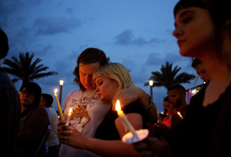 Image: Lucinda Rex, right, and Clarity Thorne embrace during a candlelight vigil downtown for the victims of a mass shooting at the Pulse nightclub