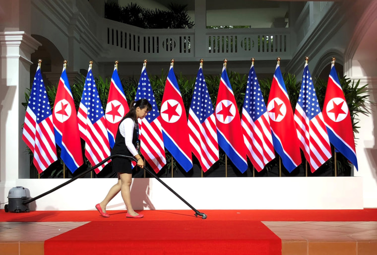 Image: Worker vacuums spot where U.S. President Trump and North Korea's leader Kim are expected to shake hands at start of their summit in Singapore