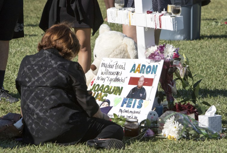 A mourner visits a cross for Aaron Feis during a vigil for the 17 people killed at Marjory Stoneman Douglas High School.
