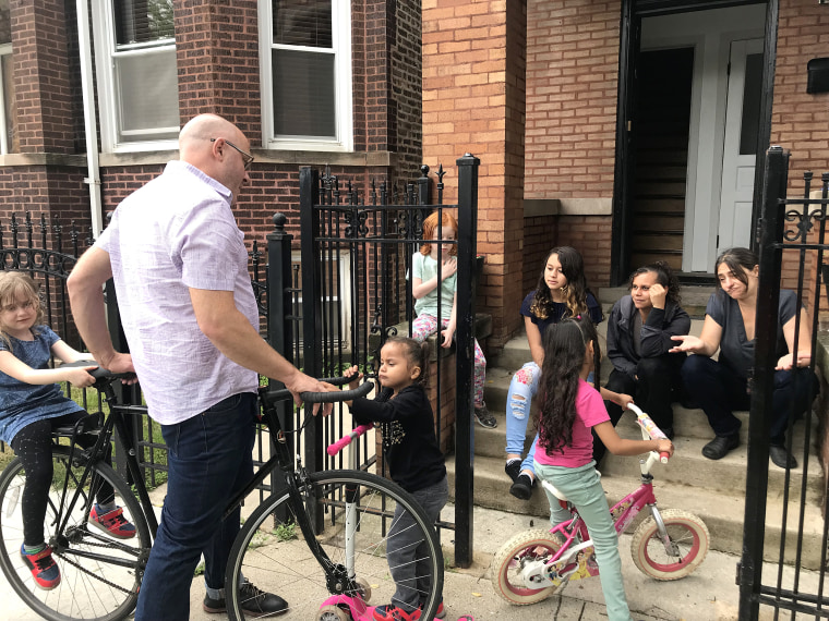 Image: Pete DeMay and Liz Gres help Perla and Skarleth learn how to ride scooters and bicycles alongside their own children, Maggie and Anthony, in Chicago.
