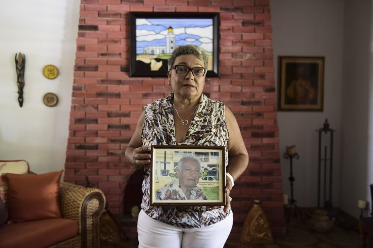Image: Nerybelle Perez poses with a portrait of her father, World War II veteran Efrain Perez