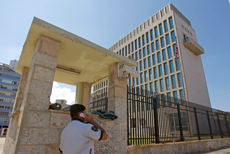 Image: A security guard uses a phone outside of the U.S. Embassy in Havana