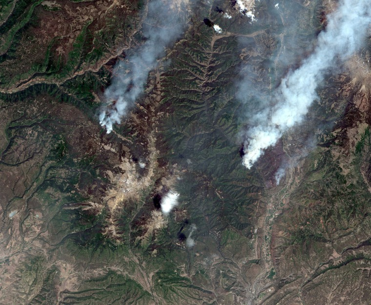 Image: A satellite image shows the Burro Wildfire (L) and the 416 Wildfire burning west of Highway 550 and northwest of Durango, Colorado