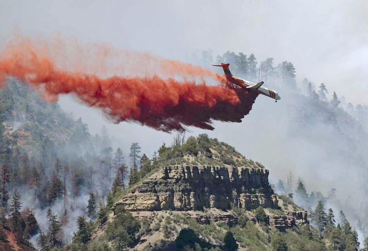 Image: An aircraft makes a fire retardant drop on a wildfire in the mountains and forests near Durango, Colorado