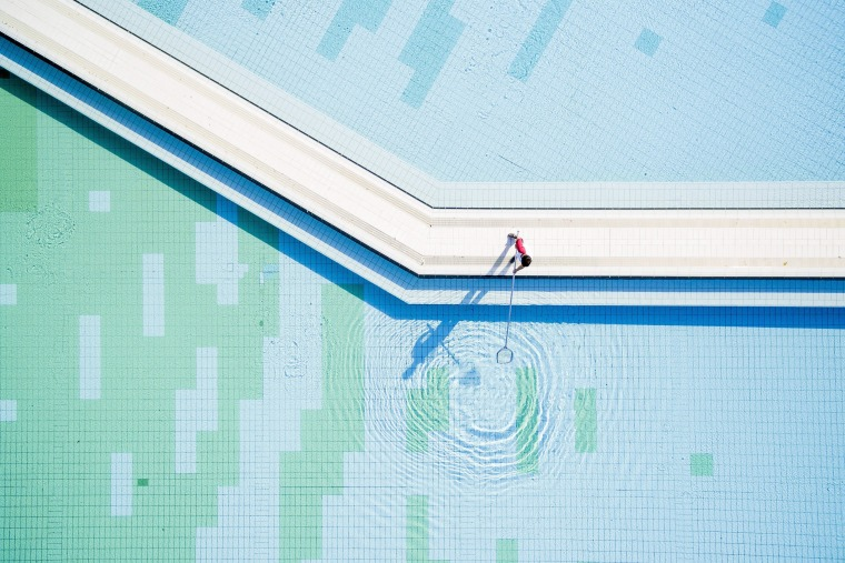 Image: A worker cleans a pool at a spa in Harkany, Hungary