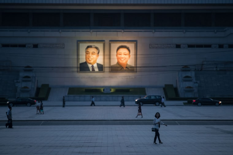 Image: Pedestrians make their way past the portraits of late North Korean leaders