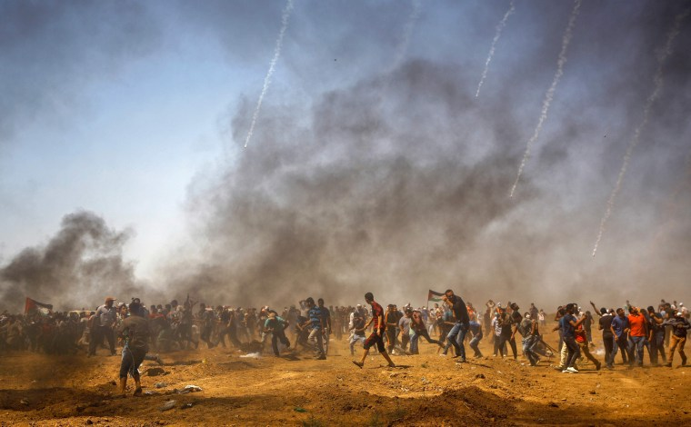 Image: Palestinian protesters take cover from tear gas during a demonstration along the border with Israel