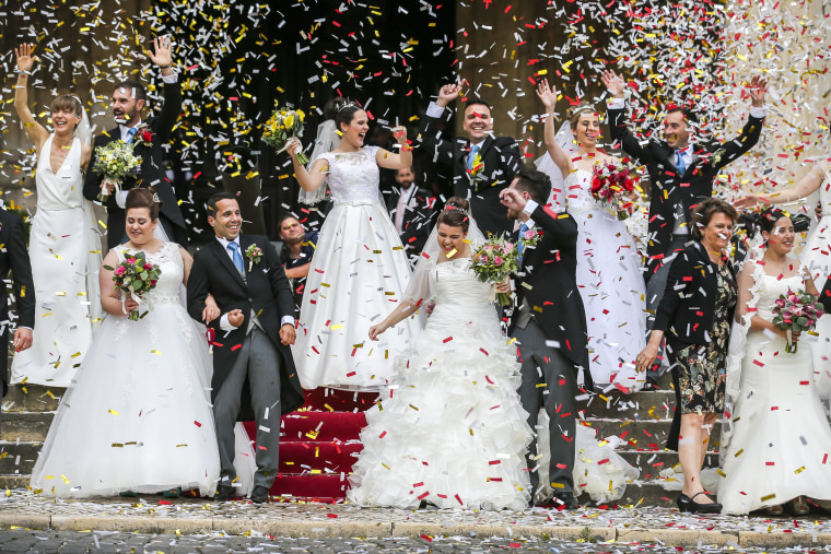 Image: Newlywed couples pose after getting married at the Cathedral of Lisbon in Portugal