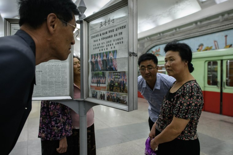 Image: Commuters read the latest edition of the Rodong Sinmun newspaper in Pyongyang