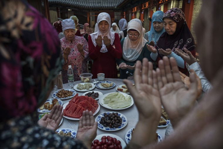 Image: Women from the Hui Muslim community pray over food before breaking their fast