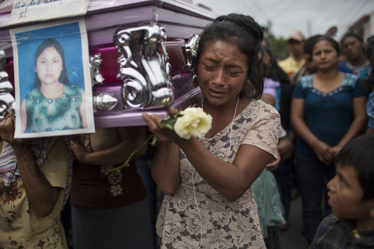 Image: Yoselin Rancho cries as she carries the remains of her best friend, Etelvina Charal, who died from the eruption of the Volcano of Fire