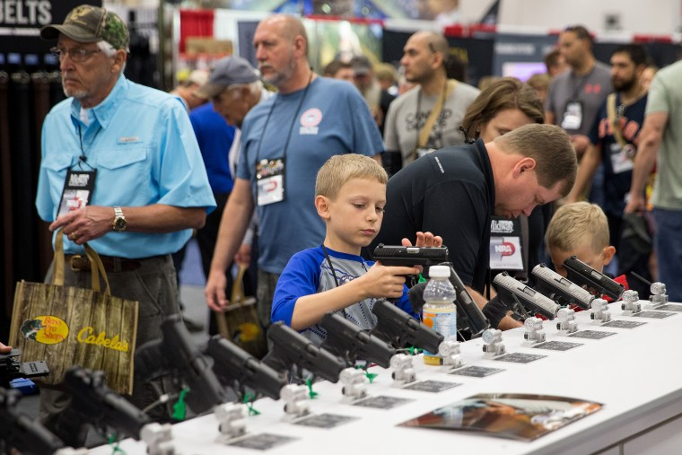 Image: A young boy inspects a firearm in an exhibit hall at the NRA's annual convention on May 5, 2018 in Dallas.