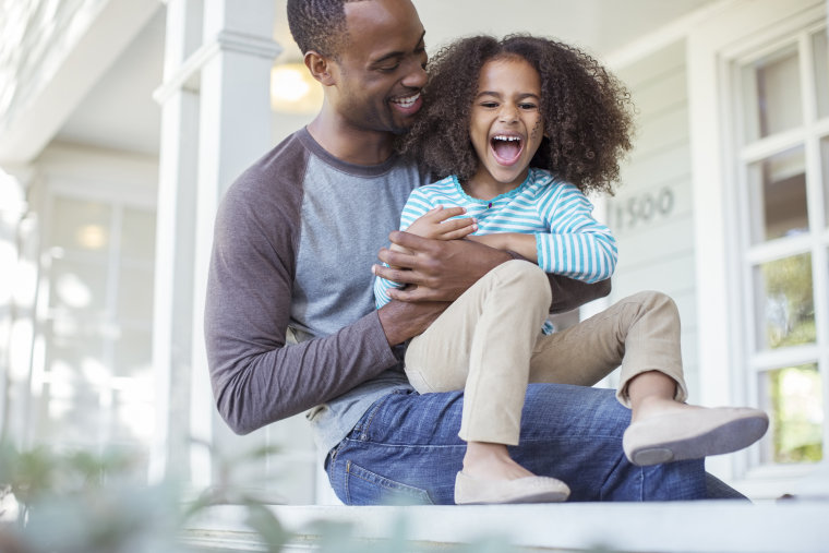 Image: Father tickling daughter on porch