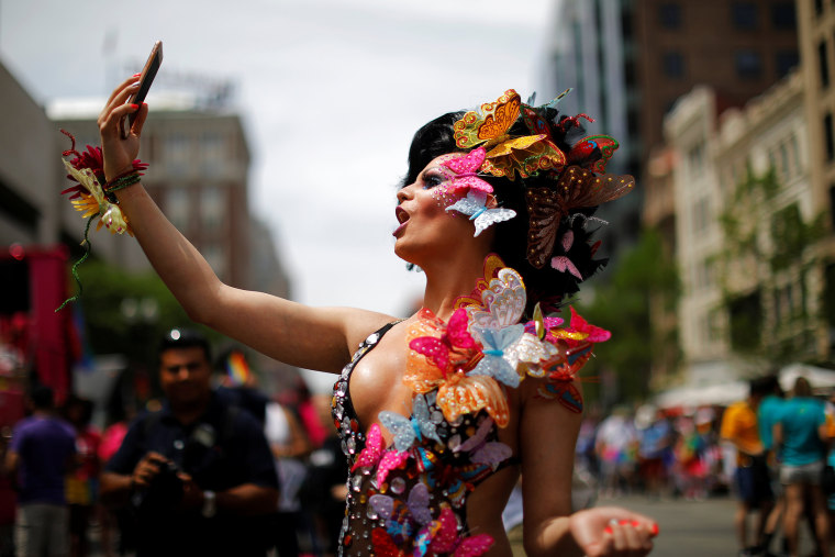 Image: Karol Barrensche records a video of herself before marching in Boston's 48th Pride Parade in Boston