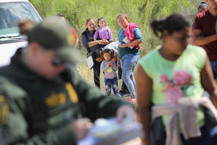 Image: Central American asylum seekers wait as U.S. Border Patrol agents take them into custody