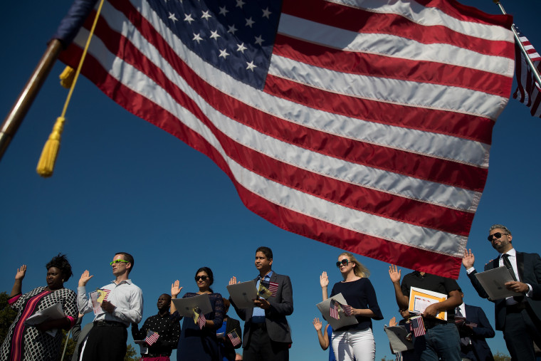 Image: An American flag billows in the wind as immigrants stand and take the oath of allegiance