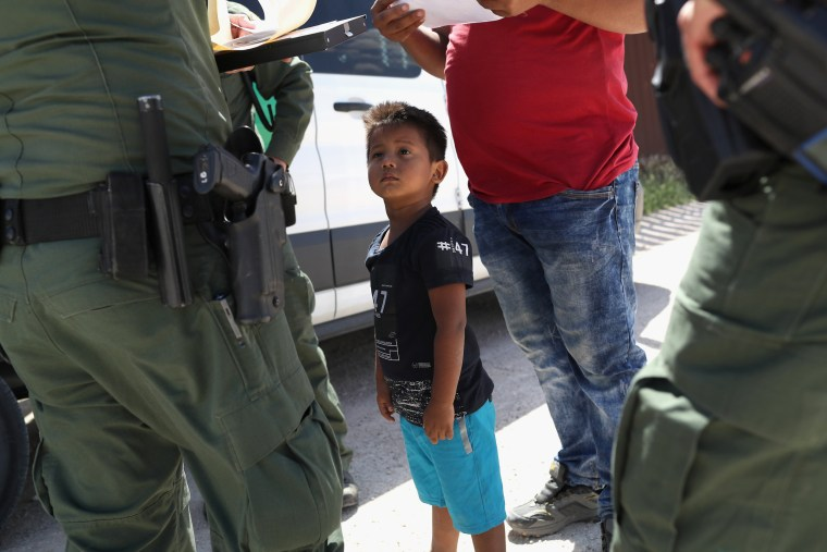 Image: A boy and father from Honduras are taken into custody by U.S. Border Patrol agents