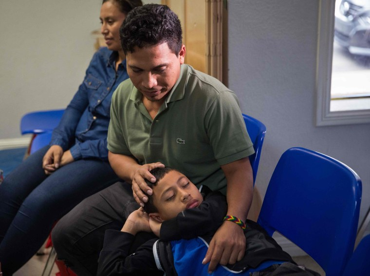 Image: An immigrant from El Salvador and his 10-year-old son wait after being released from detention