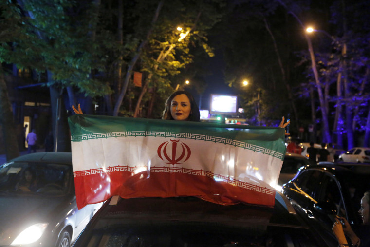 Image: A woman holds a flag while celebrating Iran's victory against Morocco in the FIFA World Cup 2018