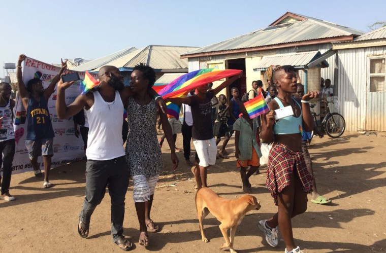 Image: Participants hold rainbow flags during an LGBTQ pride event at the Kakuma Refugee Camp in Kenya