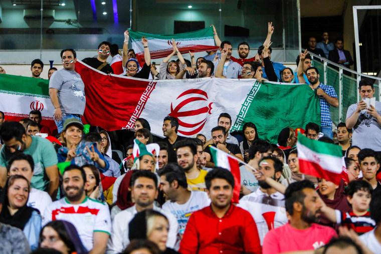 Image: People wave flags in Azadi stadium in Tehran