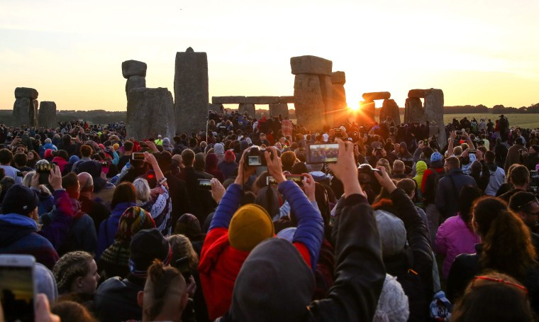 Image: Revelers watch the sunrise as they welcome the summer solstice