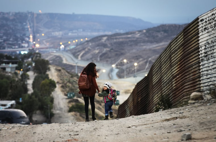 Local residents walk along the Mexico side of the U.S.-Mexico border on June 19, 2018 in Tijuana, Mexico. U.S. President Trump's Mexican border policy has raised worldwide controversy in recent days as Republicans attempt to pass an immigration reform bill.