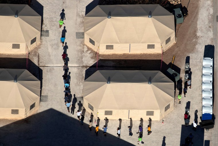Image: Immigrant children are led by staff in single file between tents at a detention facility in Tornillo, Texas