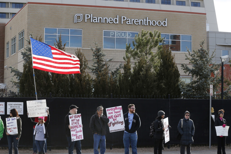 In this Feb. 11, 2017 file photo, pro-choice counter-protesters hold signs supporting a woman's right to choose abortion, as nearby anti-abortion activists held a rally in front of Planned Parenthood of the Rocky Mountains in Denver.