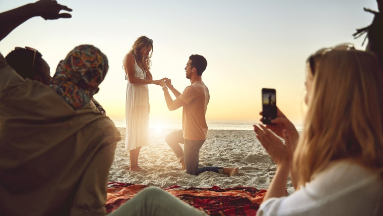 Man proposing to woman on sunny summer beach with friends