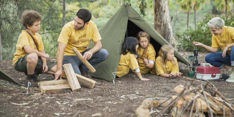 Camp counsellors and children camping in forest